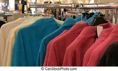 A number of different multicolored bathrobes on the hanger in the store of the shopping center