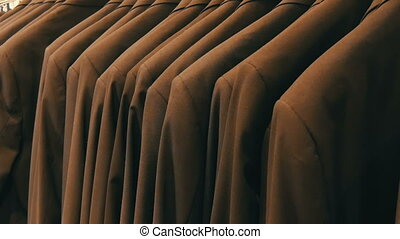 Number of identical-colored men's suits hanging on a hanger...