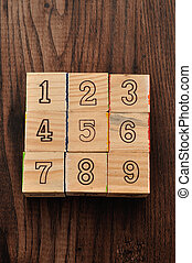 Number one to nine on alphabet blocks displayed on a wooden background