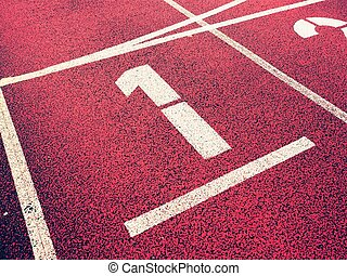 Number one. White athletic track number on red rubber racetrack