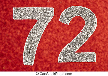 Number seventy-two silver color over a red background....