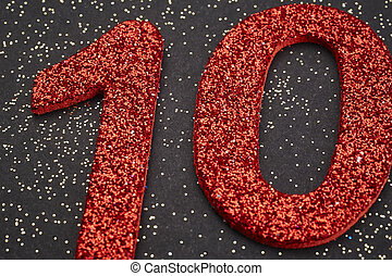 Number ten red color over a black background. Anniversary