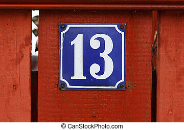 Number thirteen on red fence