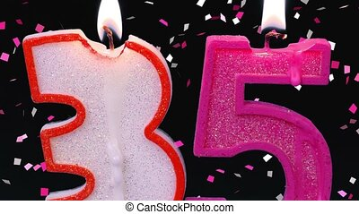 Number thirty five shaped burning candles on black with...