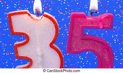 Number thirty five shaped burning candles on blue with...