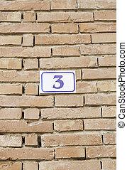 Number three on a brick wall