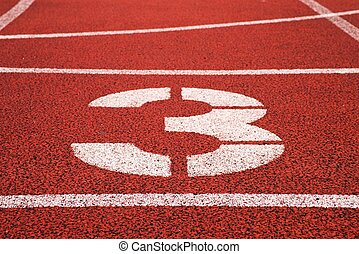 Number three. White track number on red rubber racetrack, texture of racetracks in stadium