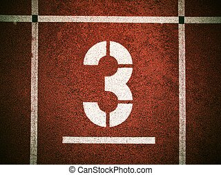 Number three. White track number on red rubber racetrack, texture of running racetracks in athletic stadium