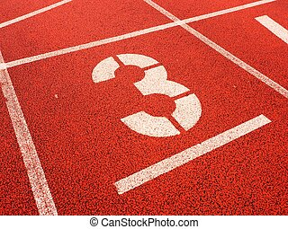 Number three. White track number on red rubber racetrack,