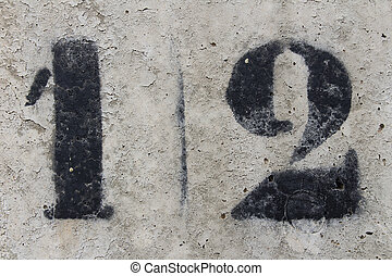 number twelve painted stencil on concrete wall