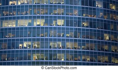 Numerous offices behind windows of an office building