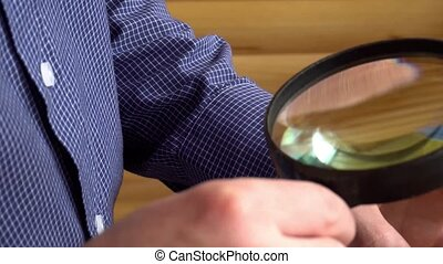 numismatist considers old coins through magnifying glass.