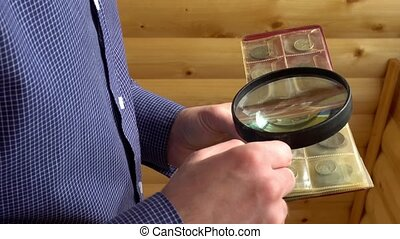 numismatist considers old coins through magnifying glass