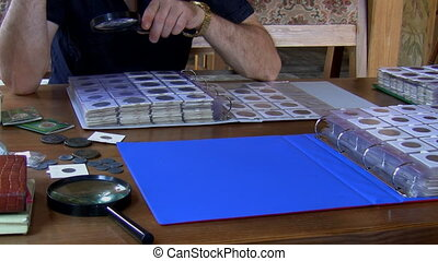 Numismatist examining coin collecti - A man numismatist is...