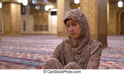 Nun in Robe Sits on a Carpet Inside an Islamic Mosque. Egypt...
