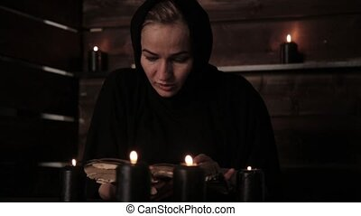 Nun is reading old book highlights the flame of a candle....