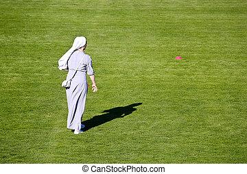 Nun on green soccer field
