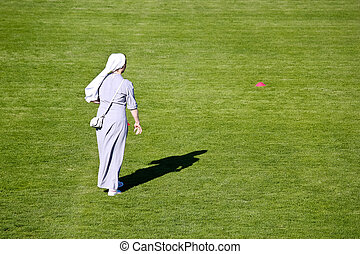 Nun on green soccer field
