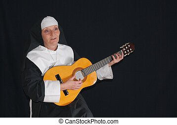 Nun playing the guitar - Middle aged nun playing the guitar....