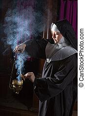 Nun preparing incense for mass - Young nun preparing an...