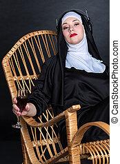 Nun with wine in headphones