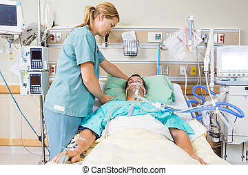Nurse Adjusting Patient's Pillow - Friendly nurse adjusting...