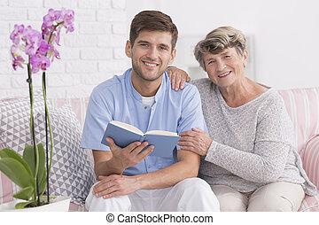 Nurse and elder women on a couch - Male nurse sitting on a...