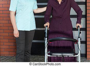 Nurse and elderly woman in a walker outside