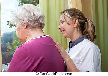Nurse and elderly woman standing at the window