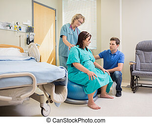 Nurse And Man Assisting Pregnant Woman On Exercise Ball -...