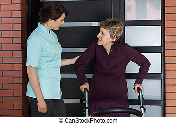 Nurse and older woman standing in front of house