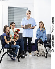 Nurse And Owners With Pets In Clinic's Waiting Area