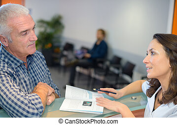 nurse and patient conversing at reception desk in hospital