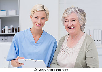 Nurse and patient smiling in clinic