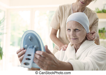 Nurse and patient with cancer wearing headscarf and looking at her reflection in the mirror.