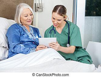 Female caretaker and senior woman using tablet PC in bedroom at nursing home