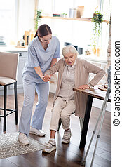 Nurse assisting aged woman in making steps after surgery
