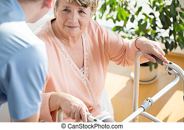 Nurse assisting disabled pensioner - Horizontal view of...