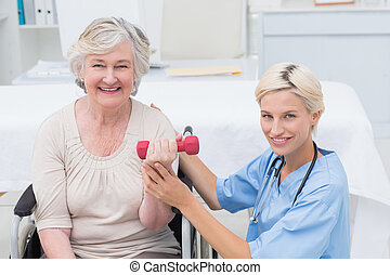 Nurse assisting female patient in lifting dumbbell