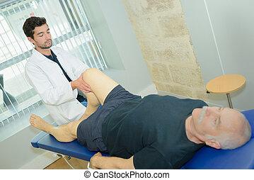 nurse assisting senior man in leg exercise