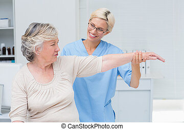 Nurse assisting senior patient in exercising at clinic