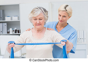 Nurse assisting senior woman in exercising with resistance band