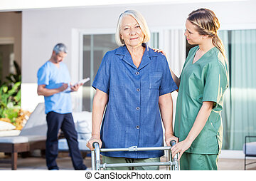 Nurse Assisting Senior Woman To Walk With Zimmer Frame -...