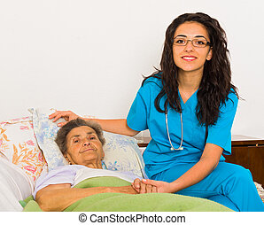 Nurse at Home - Kind nurse woman with senior patient at...