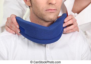 Nurse attaching a neck brace for a male patient