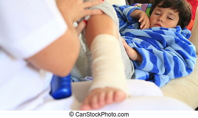 Nurse bandaging little boy ankle - Doctor/nurse hands...