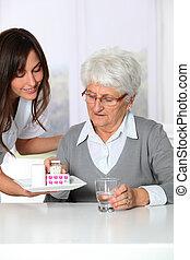 Nurse bringing medicine to elderly woman