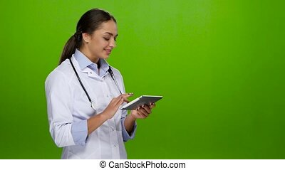 Nurse browses information on the tablet pc and cute smiles