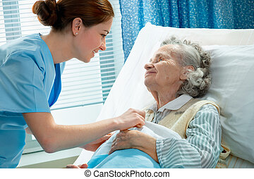 care - Nurse cares for a elderly woman lying in bed