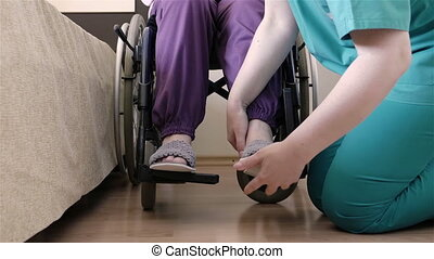 Nurse caring of elder disabled woman in wheelchair - Young...